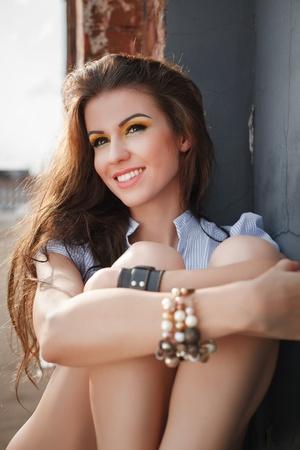 Pretty woman in blue shirt sitting near a brick wall