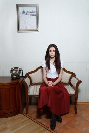 antique phone: A young woman is sitting in an old chair. Stock Photo