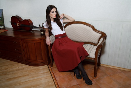 A young woman is sitting in an old chair. photo