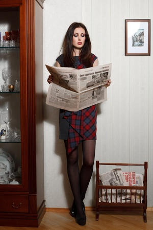 newspaper reading: A young woman is reading the newspaper. Stock Photo