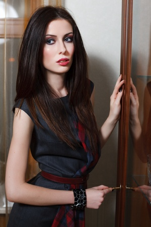A young woman is standing near an old sideboard. photo