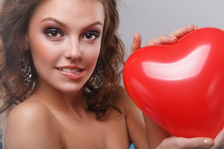 Close-up of a young, beautiful, brown-haired woman with red balloon. photo