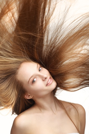 Pretty young girl with long flying hair on white background Stock Photo - 11854870