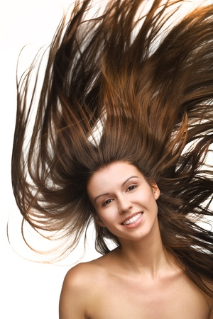 Pretty young girl with long flying hair on white background photo