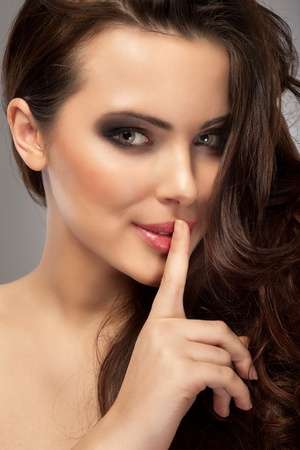 a portrait of a beautiful brunette with a finger on her lips showing to keep silence, hush photo