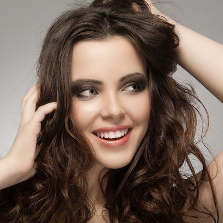beautiful girl face: Very beautiful and happy woman hands in her hair pulling. Stock Photo