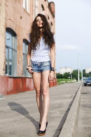 pantalones cortos: Chica muy guapa caminando por la calle a lo largo del edificio de ladrillo