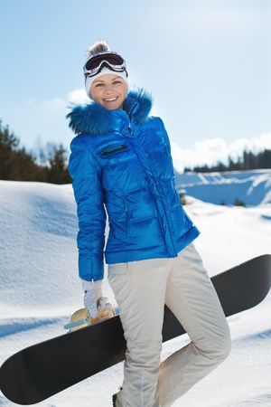 a beautiful young girl with a snowboard in his hands stands on a hillside photo