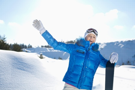 sunny cold days: a beautiful young girl with a snowboard standing on a hillside