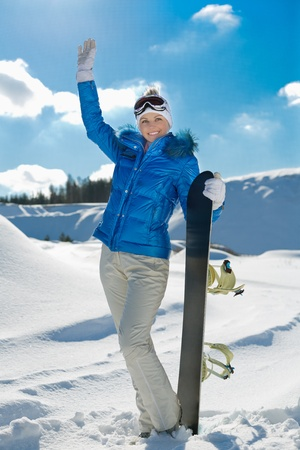 a beautiful young girl with a snowboard standing on a hillside Stock Photo - 12645996