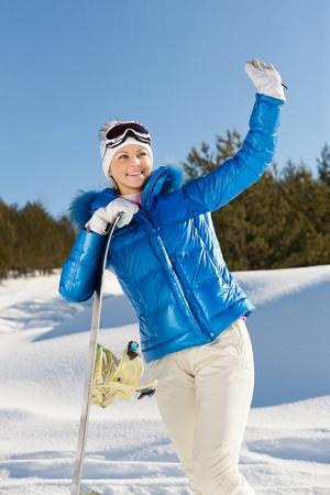 a beautiful young girl with a snowboard in her hand standing on a hillside Stock Photo - 12646020