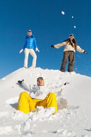 Three young people are enjoying the snow and sun photo