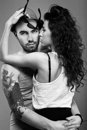 The portrait of a sexy girl and a hot man standing face to face  with his arm round her waist pulling her closer photo