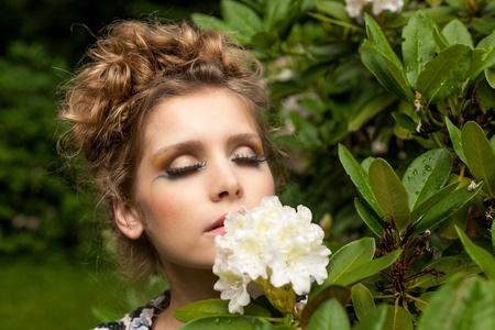 Ragazza molto bella è odorando un fiore