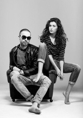 A beautiful young couple sitting in a chair photo