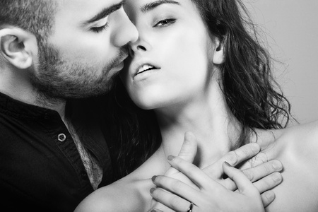 a hot man is kissing his  beautiful young woman photo