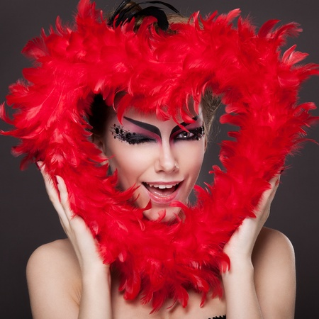 Beauty face of beautiful woman with makeup is holding a red heart photo