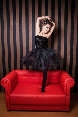 Beautiful ballerina is dancing on the couch photo