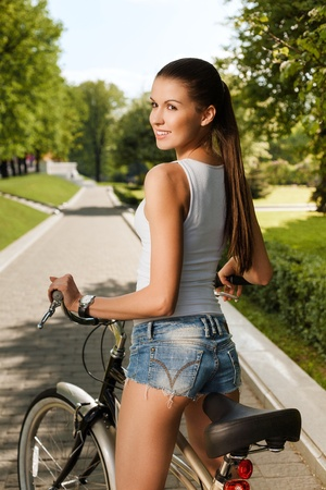 A beautiful young girl is sitting on a bicycle - Outdoors Stock Photo