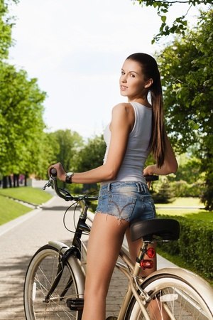 A beautiful young girl is sitting on a bicycle - Outdoors Фото со стока