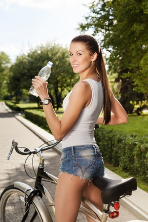 A young beautiful girl is drinking water from a bottle while sitting on a bicycle - Outdoors photo