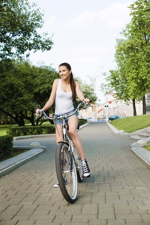 A beautiful young girl is sitting on a bicycle - Outdoors photo