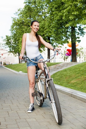 girl on bike: A beautiful young girl is sitting on a bicycle - Outdoors Stock Photo
