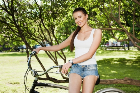 A beautiful young girl in a white T-shirt and blue jeans is sitting a bicycle - Outdoors photo