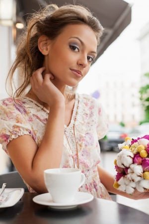 bar chair: A beautiful young woman are sitting in a cafe and drinking tea. Outdoors Stock Photo
