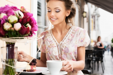 A young woman are eating a dessert  Holding a cup of tea  Outdoors