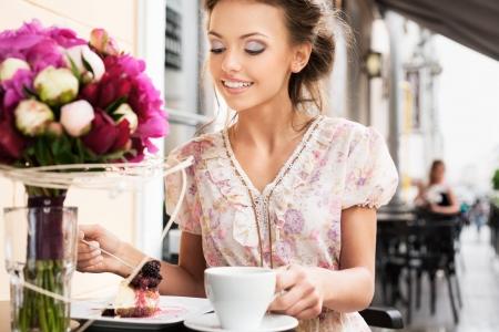Eine junge Frau isst ein Dessert hält eine Tasse Tee Freien Standard-Bild