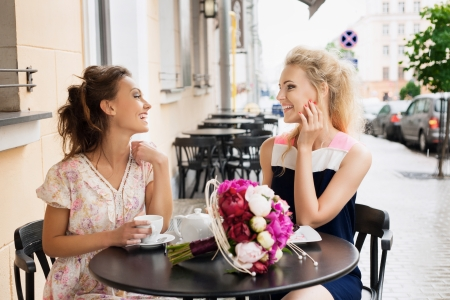 Two beautiful young women with great smile and hairstyle sitting at a bar, drinking tea and coffee  Stock Photo