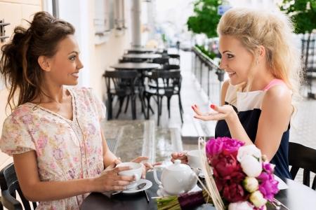 habladur�as: Dos mujeres j�venes con gran sonrisa y peinado sentado en un bar, bebiendo t� y caf�