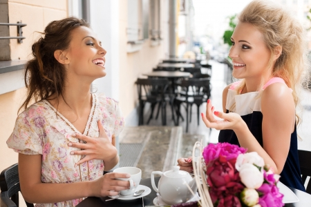 Two beautiful women with great smile and hairstyle sitting at a bar, drinking tea and coffee  Stock Photo
