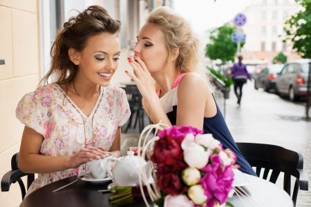 socializando: Dos hermosas mujeres j�venes con gran sonrisa sentado en un bar, bebiendo t� y caf�