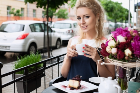 bar chair: A beautiful young woman are drinking tea  Holding a cup of coffee  Outdoors