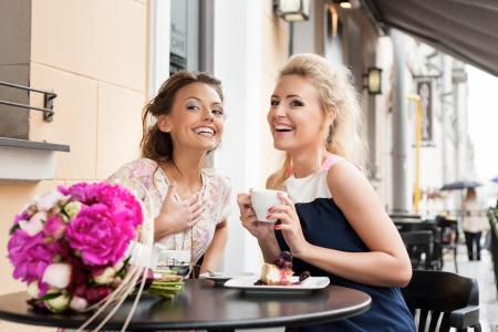 Two beautiful young women with hairstyle sitting at a cafe, drinking tea and coffee  - outdoors Stock Photo