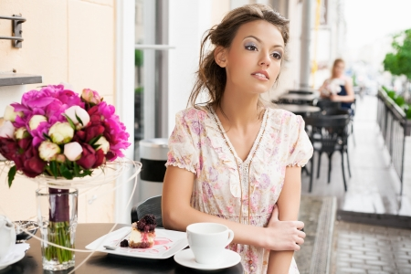 A beautiful girl are sitting in a cafe and drinking tea. Outdoors Stock Photo - 14329921