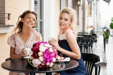Two beautiful women with great smile and hairstyle sitting at a bar, drinking tea and coffee. outdoors photo
