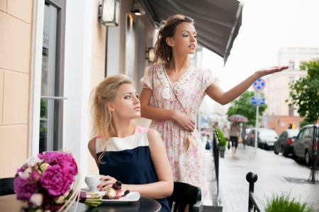 Portrait of two young women having coffee after a day of shopping. Outdoors photo