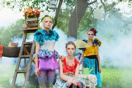 Three young beautiful ladies in a garden. Outdoors photo