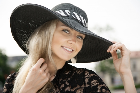Portrait of young girl standing in black hat outdoors photo