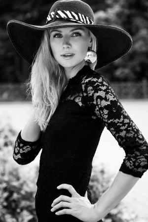 Portrait of pretty young woman standing in black hat outdoors photo