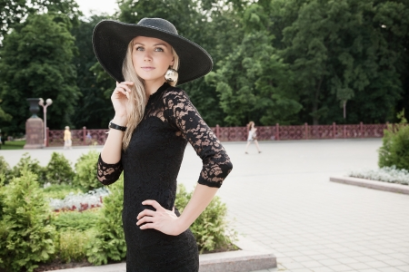 Portrait of pretty woman standing in black hat outdoors