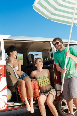 people travelling: Young people taking break  relaxing in her car near the beach - outdoors