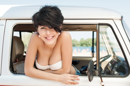 Girl smiling in car near the beach - outdoors