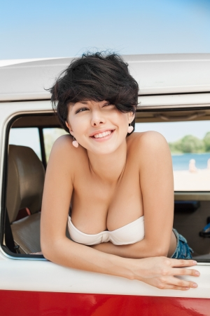Woman enjoying the sun in car near the beach - outdoors