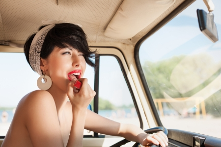 putting: pretty woman looking in rear view mirror and putting make up in car