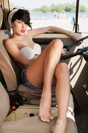 Beautiful woman relaxing in car near the beach - outdoors photo