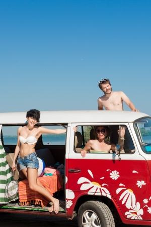 jóvenes disfrutando del sol en el coche con el cielo azul y el sol nublado en segundo plano - al aire libre